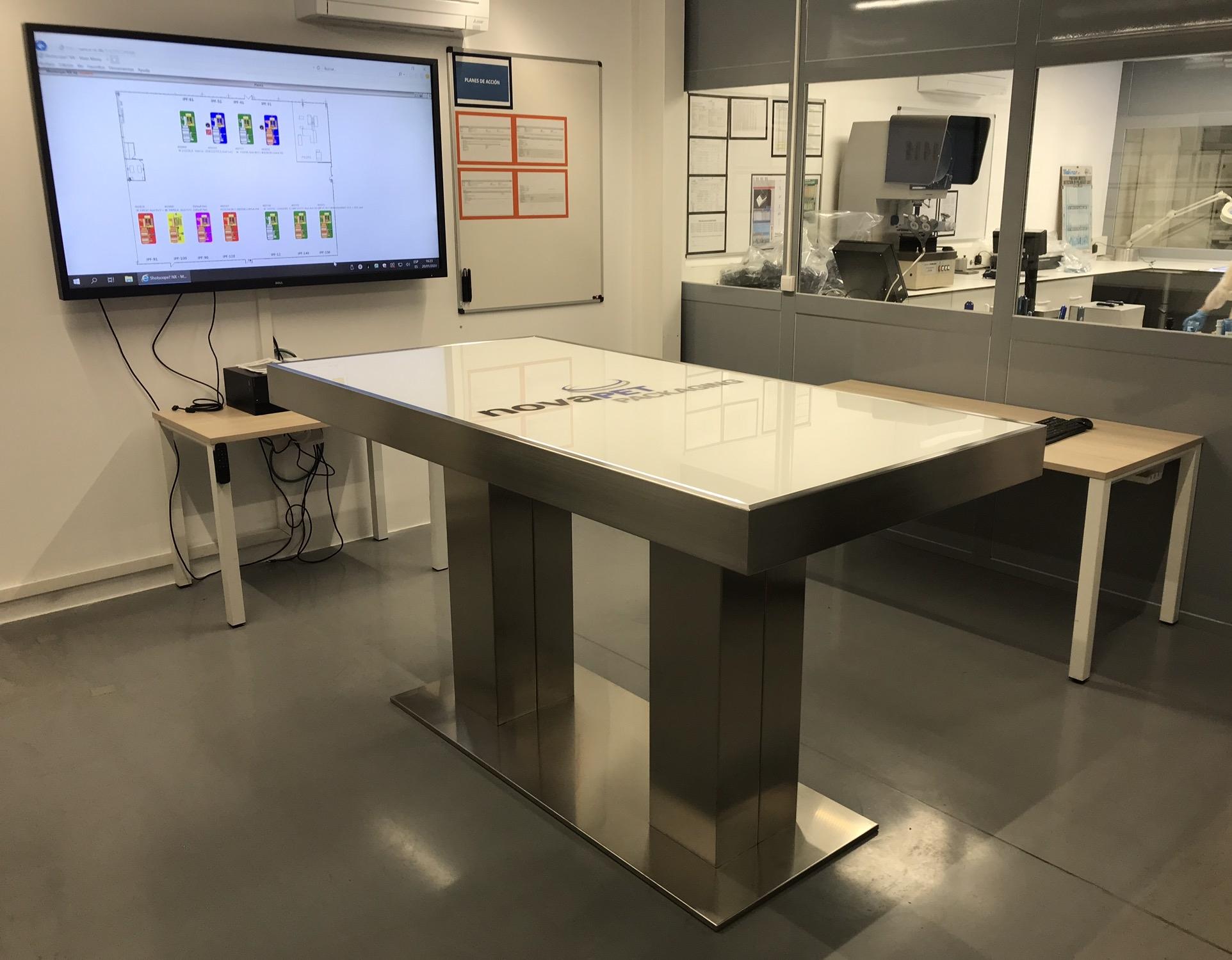 Mesa para reuniones con sobre de vidrio retroiluminado y logo